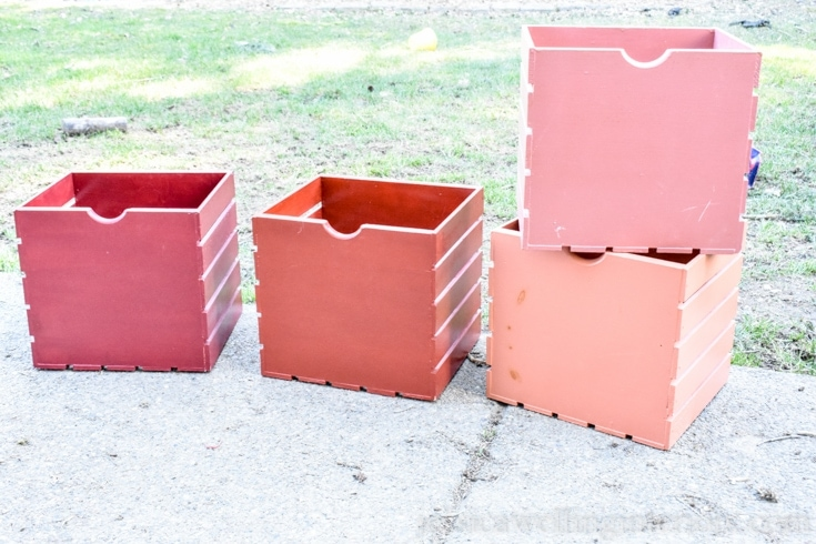 4 wood crates sitting outside. A red crate, orange create and 2 pink crates.