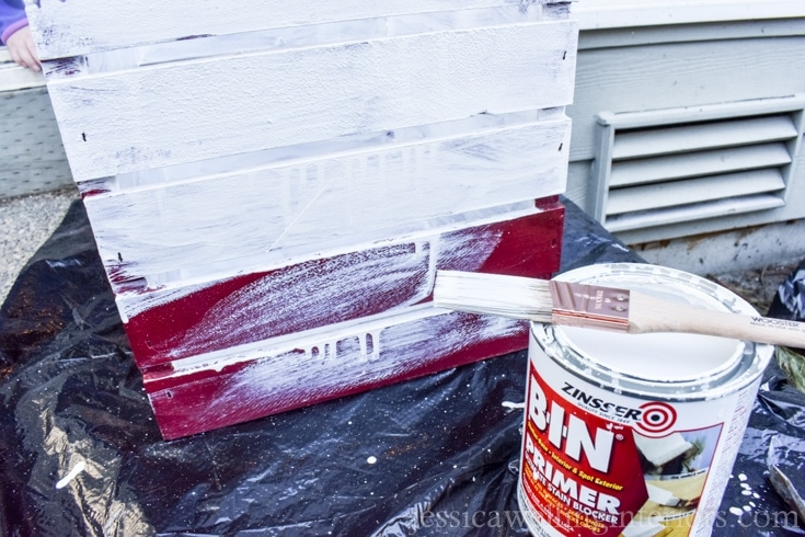 A red crate with white primer paint on the outside.