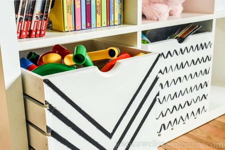 A white wood crate with black Vs painted on the front. The crate is filled with toys.