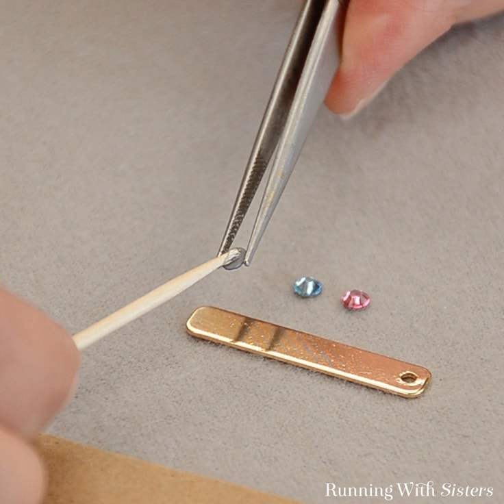 Use tweezers to hold the rhinestone and dab glue on the back.