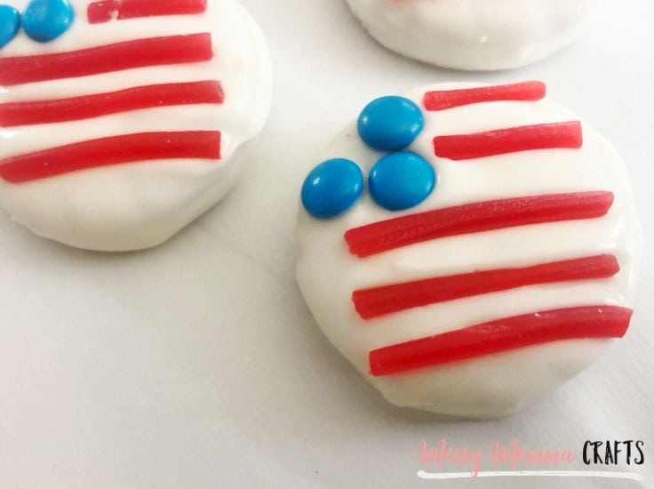 Round cookies covered in white chocolate and with blue candies and red licorice - they look like American flags.