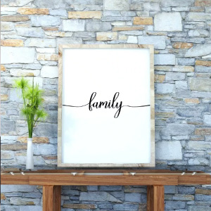 Family wall decor free printable in a frame on top of table leaning against rock wall.