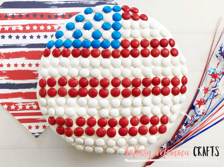 A round cake with white frosting decorated with red white and blue M&Ms to look like an American Flag.