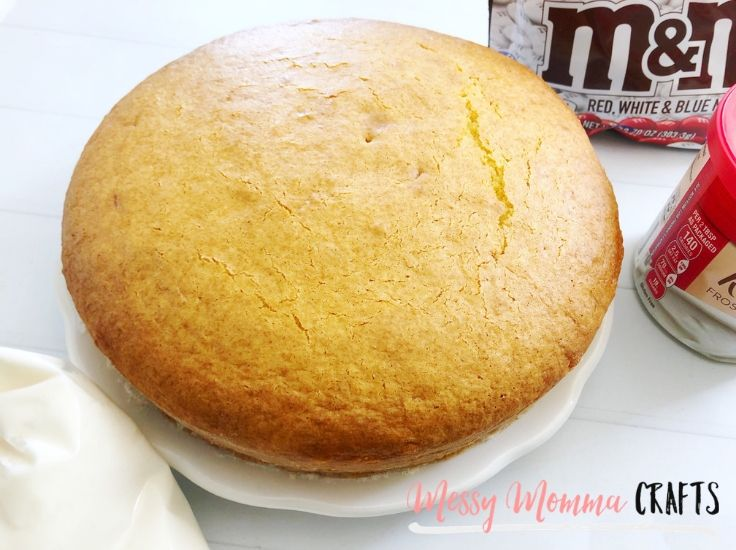 A round white cake that is outside of the pan.