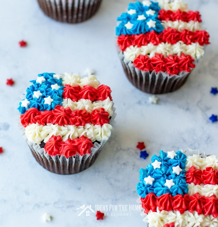 Four chocolate cupcakes decorated for the 4th of July with red, white and blue frosting to look like an American flag