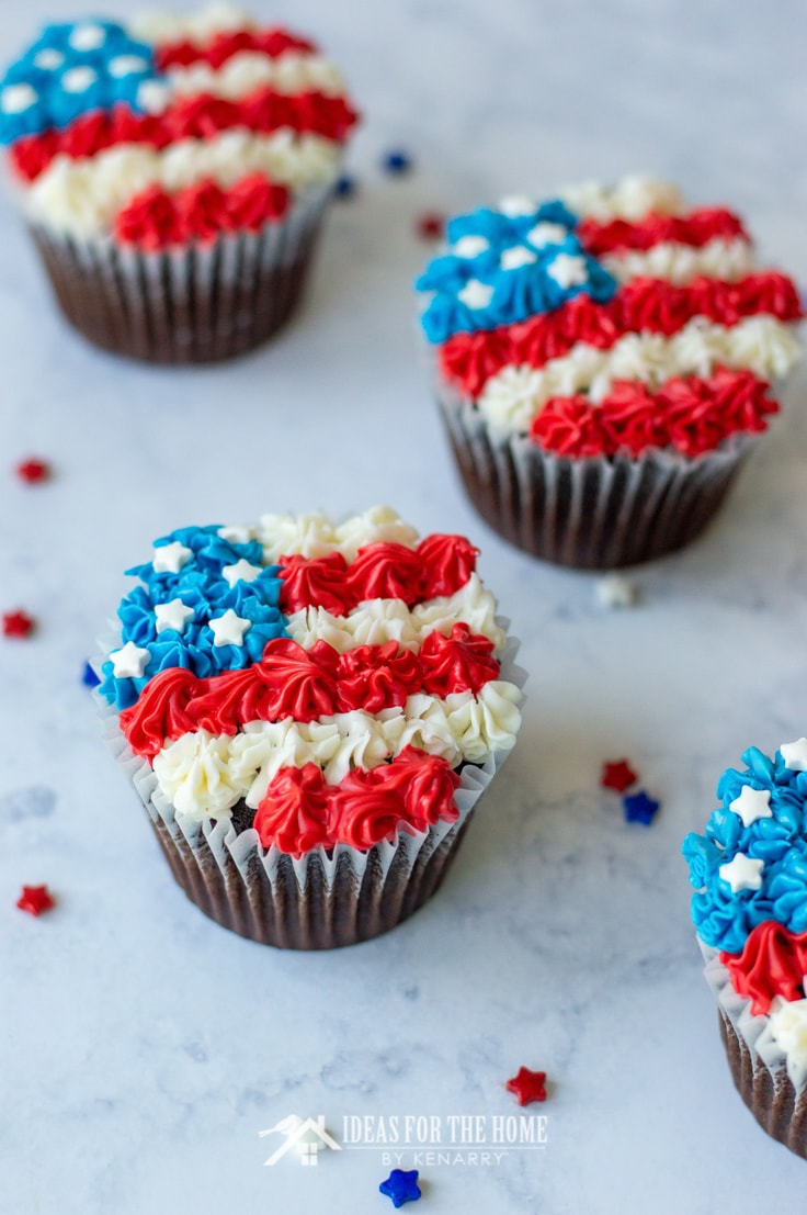 Close up of three 4th of July chocolate cupcakes decorated with red, white and blue frosting to look like an American flag