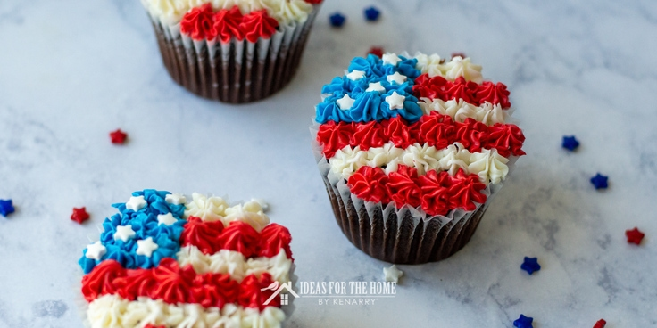 Three chocolate cupcakes for the 4th of July decorated with red, white and blue frosting to look like an American flag with star sprinkles