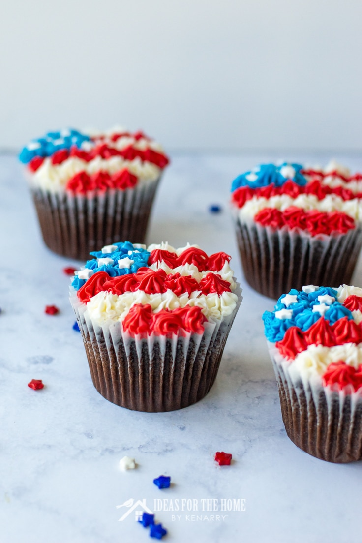 Side view of 4 chocolate cupcakes for the 4th of July decorated with red, white and blue frosting to look like an American flag
