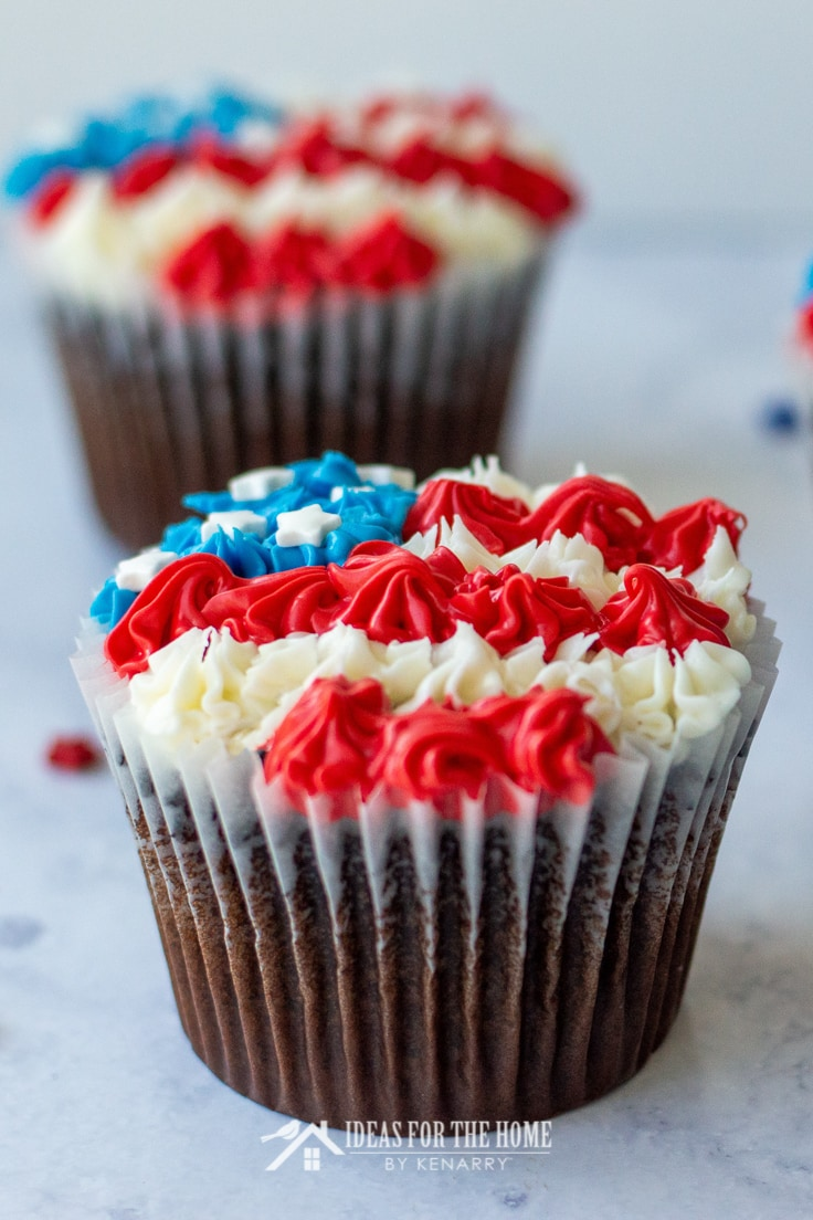 Close up of a chocolate cupcake for the 4th of July decorated with red, white and blue frosting to look like an American flag