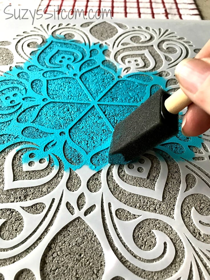 Using a sponge brush to dab blue paint on a stencil
