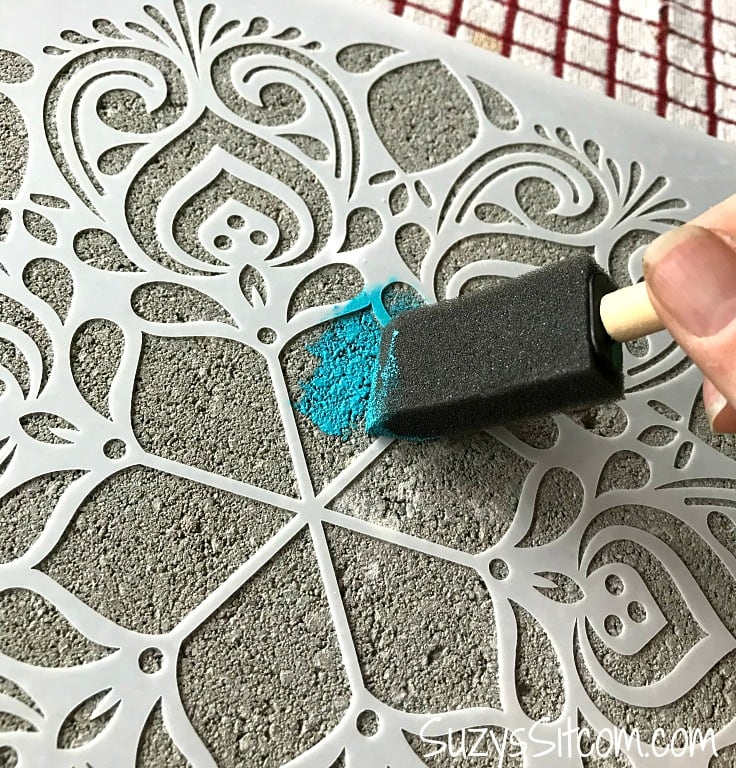 Painting a stepping stone using a stencil