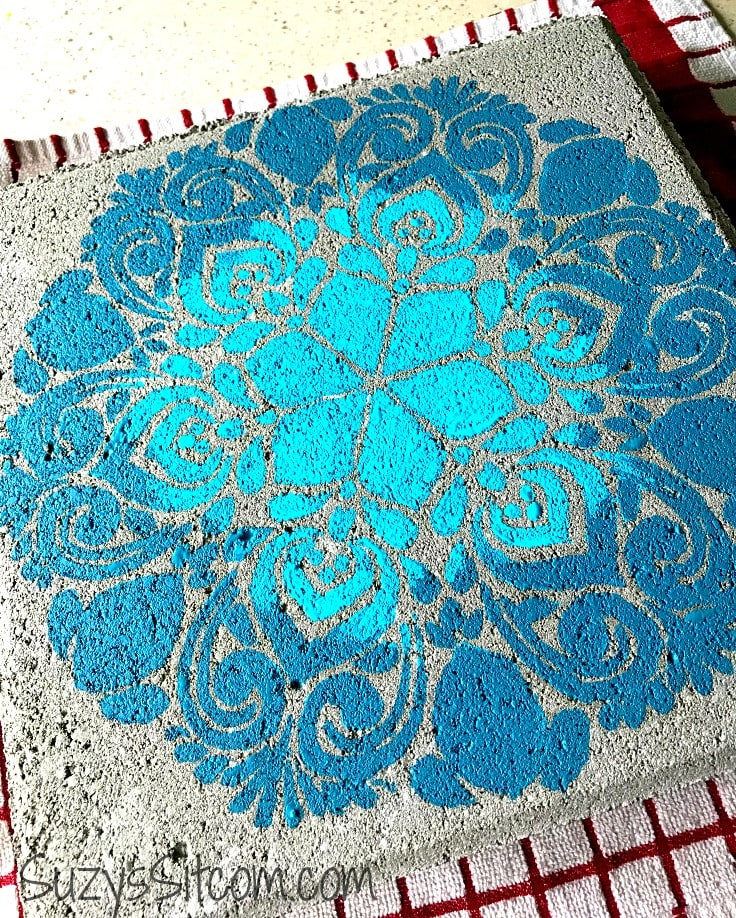 A two-toned blue floral design on a stepping stone.