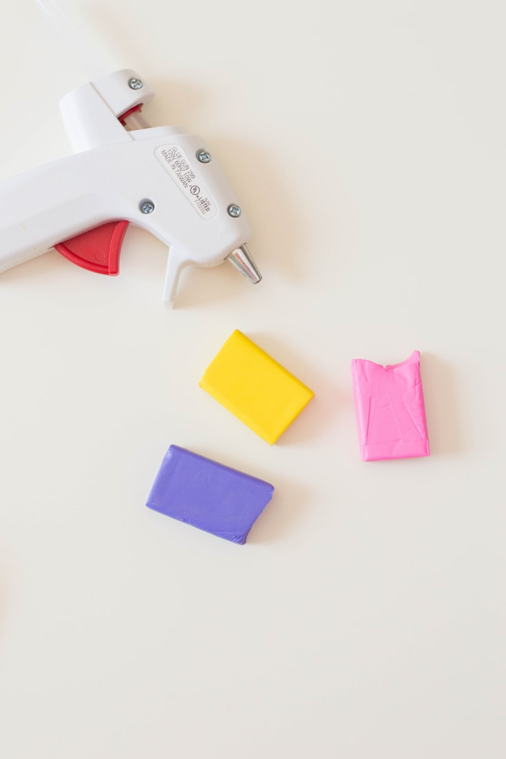 A hot glue gun with yellow, pink, and purple polymer clay blocks.