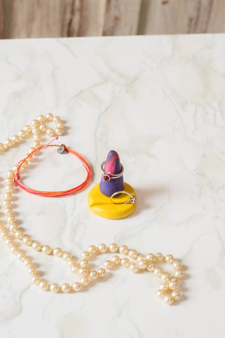 A purple and pink DIY polymer clay ring holder. Learn how to make one yourself with this tutorial.