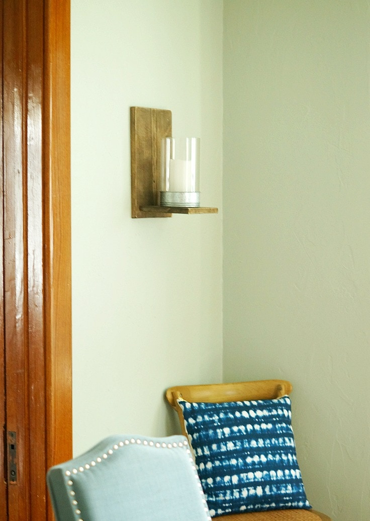 A wooden wall sconce holding a white candle.
