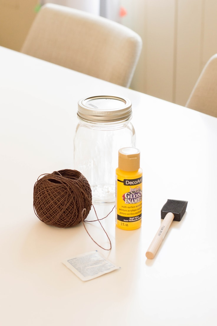Supplies you need for a DIY mason jar pencil holder - a mason jar, paint, paintbrush and brown twine.