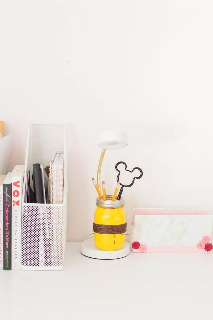 A yellow DIY mason jar pencil holder with brown twine.