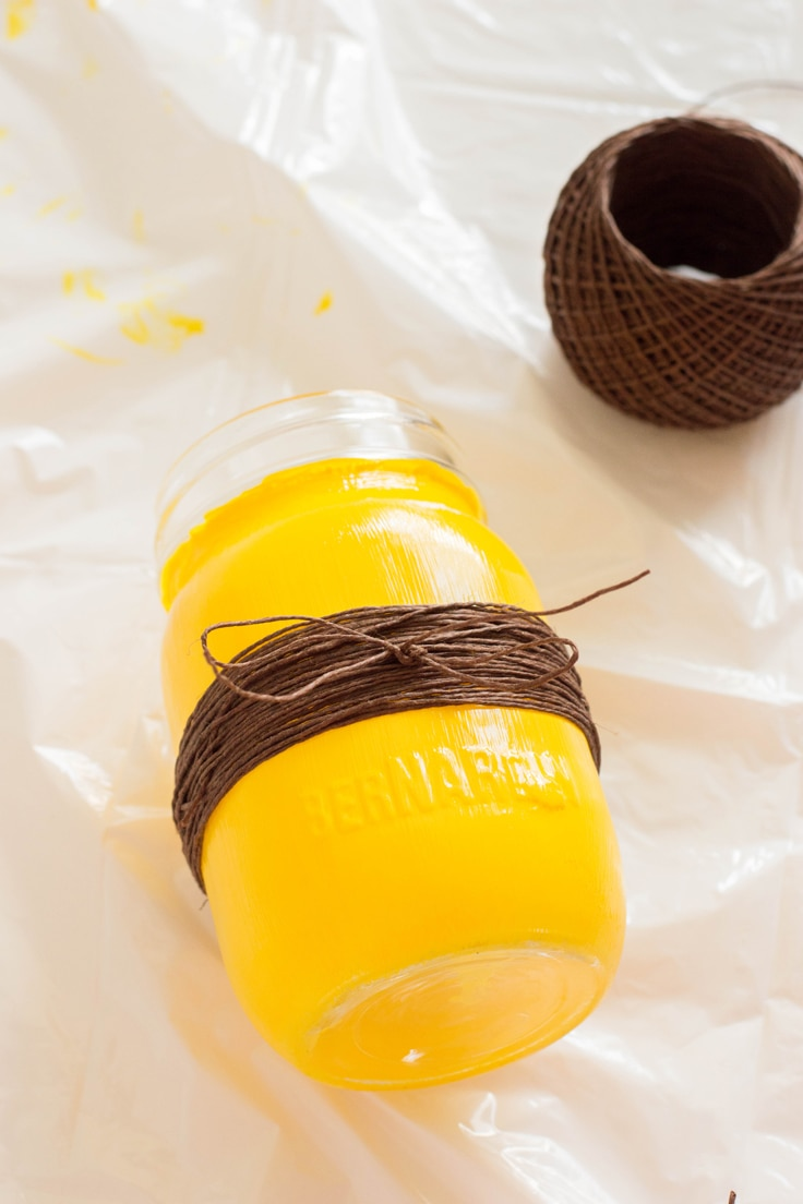 Brown twine wrapped around the yellow painted mason jar. The brown twine is tied into a bow for a finished look.