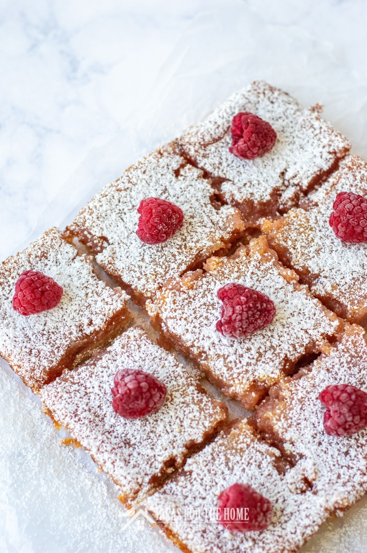 Overhead view of 8 raspberry lemon bars. This easy summer dessert for a potluck is topped with powdered sugar and fresh raspberries.