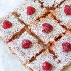 Overhead shot of raspberry lemon bars sprinkled with powdered sugar. Each of these summer desserts is topped with a single plump juicy raspberry.
