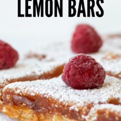 Raspberry Lemon Bars - close up of a raspberry lemon bar with a big red raspberry on the top, sprinkled with powdered sugar