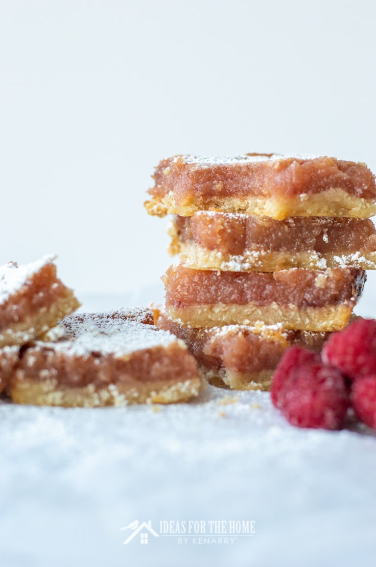 6 raspberry lemon bars, four are stacked on top of one another and two are set to the side, fresh raspberries appear near by for garnish