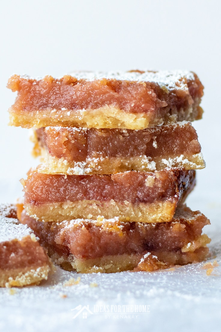 Close up of a stack of 4 dessert bars made with a buttery crust, lemon raspberry puree and topped with powdered sugar. They taste just like raspberry lemonade, only in dessert form.