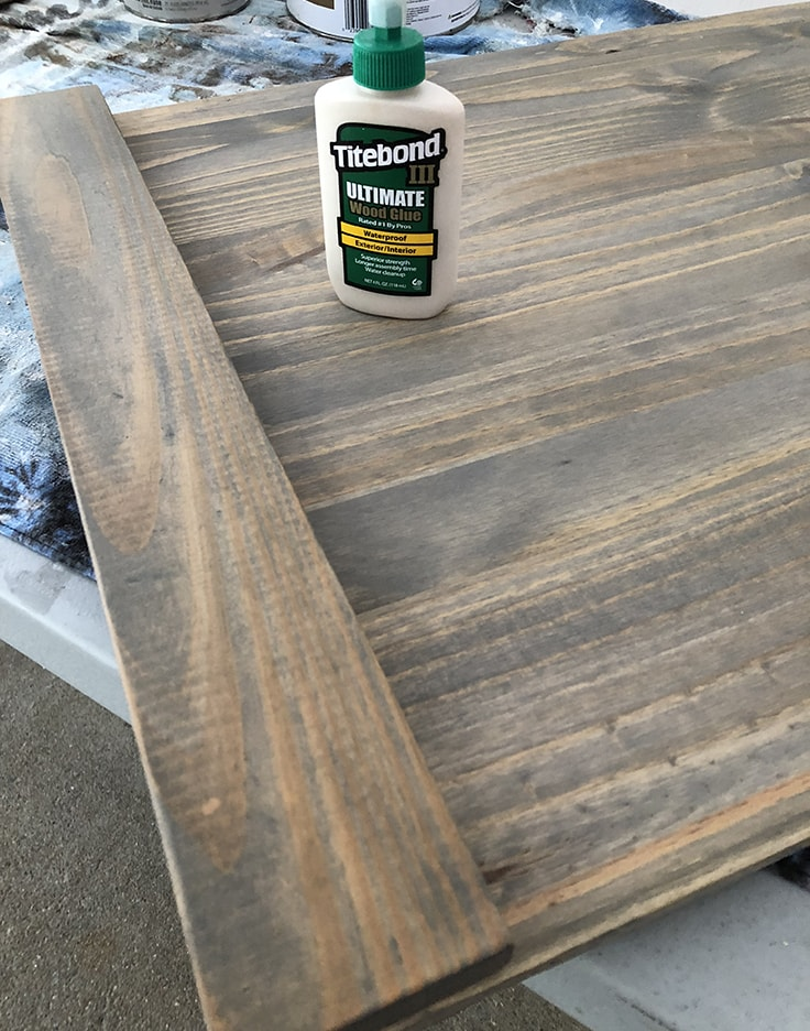 A bottle of Titebond III Ultimate Wood Glue on top of stained wood.