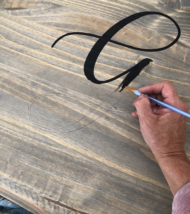 Painting a monogram onto a piece of wood