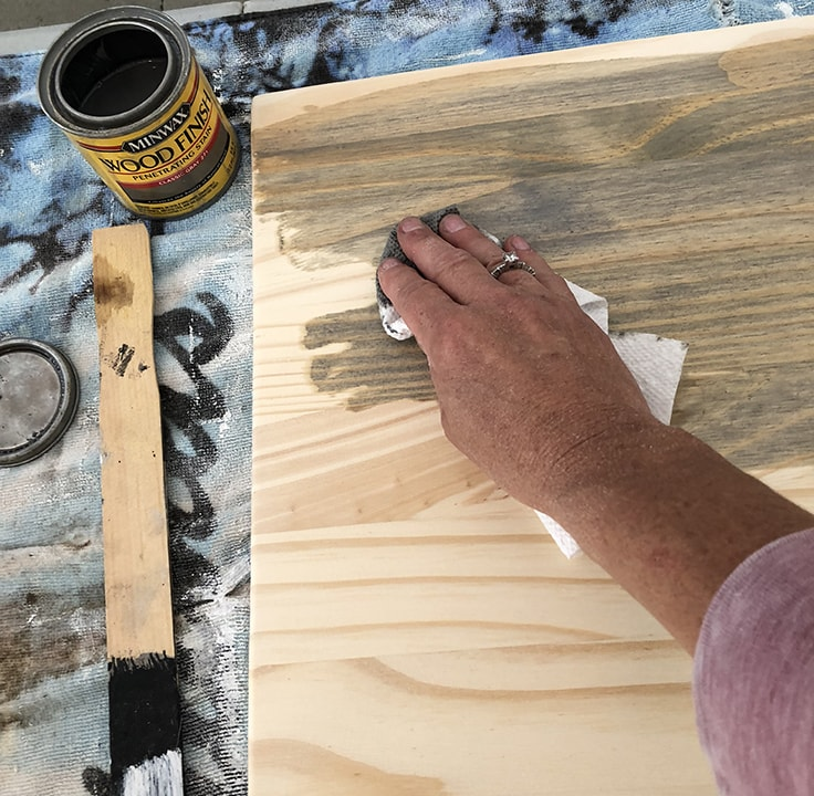 Using wood finish and a paper towel to stain a board.