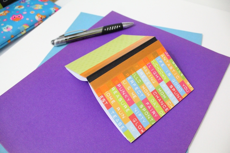 Notebook folded open on a desk to shop both covers and washi tape