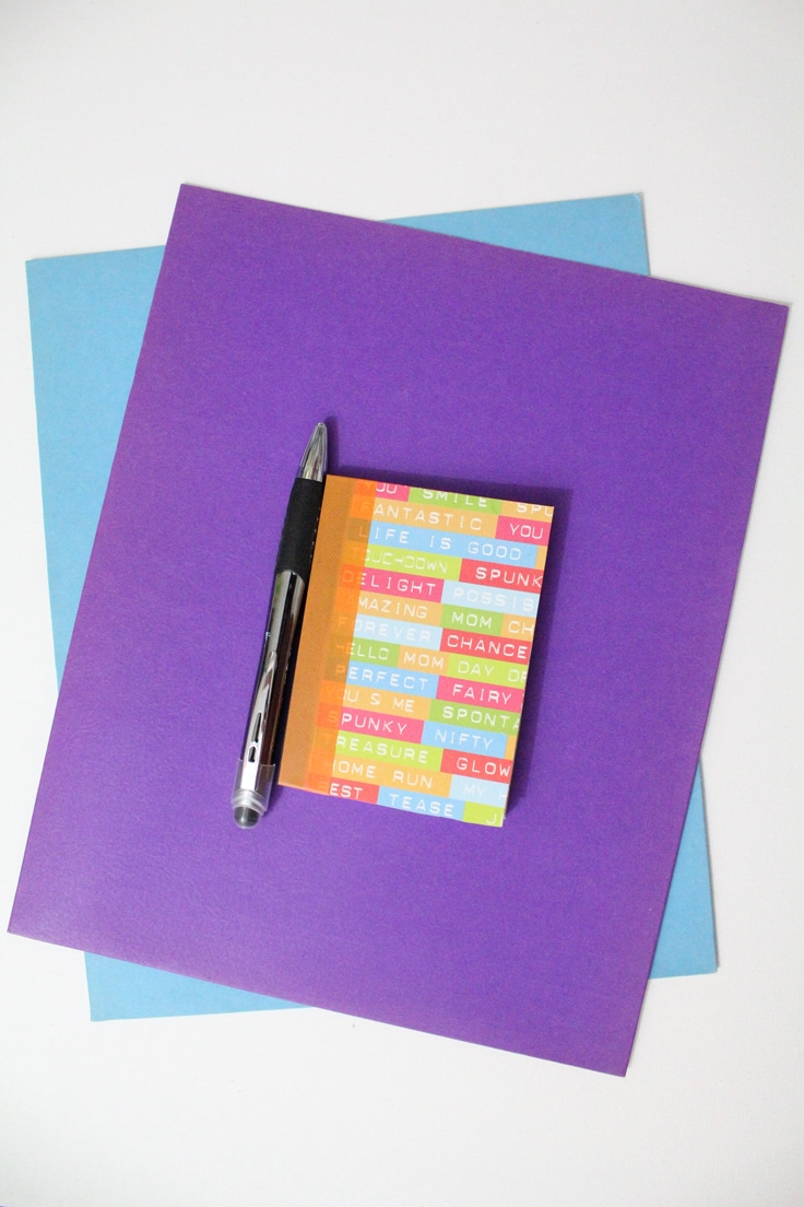 Colorful notebook stacked on top of purple and blue folders