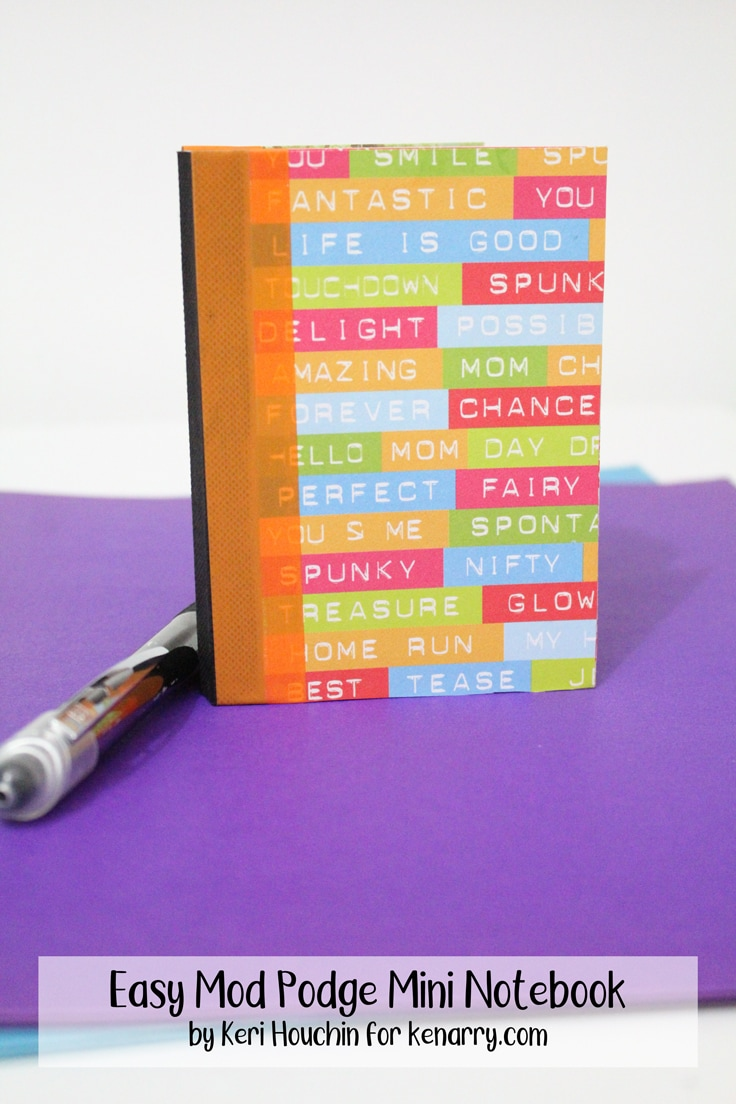 Brightly colored mini notebook standing on a purple folder beside a pen