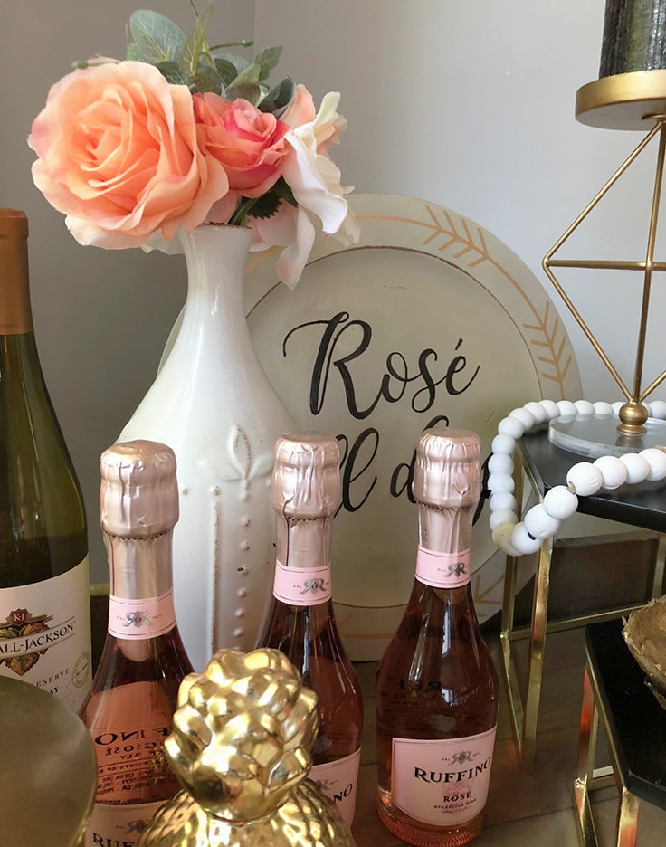 A white vase with orange and pink flowers on a rose-themed bar cart
