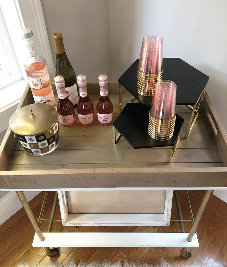 Adding pink and rose gold plastic cups to the bar cart with the rose