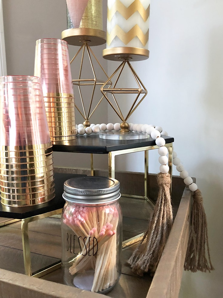 A close up of painted wood beads and a few pieces of decor for a rose gold bar cart