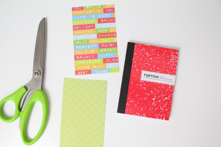 A notebook beside two pieces of scrapbook paper and a pair of scissors