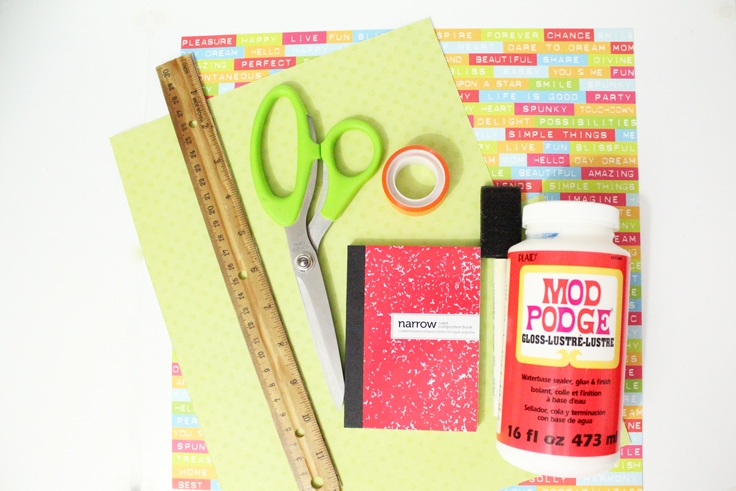 Scrapbook paper, a ruler, scissors, mini composition book, washi tape roll, and Mod Podge with a sponge brush