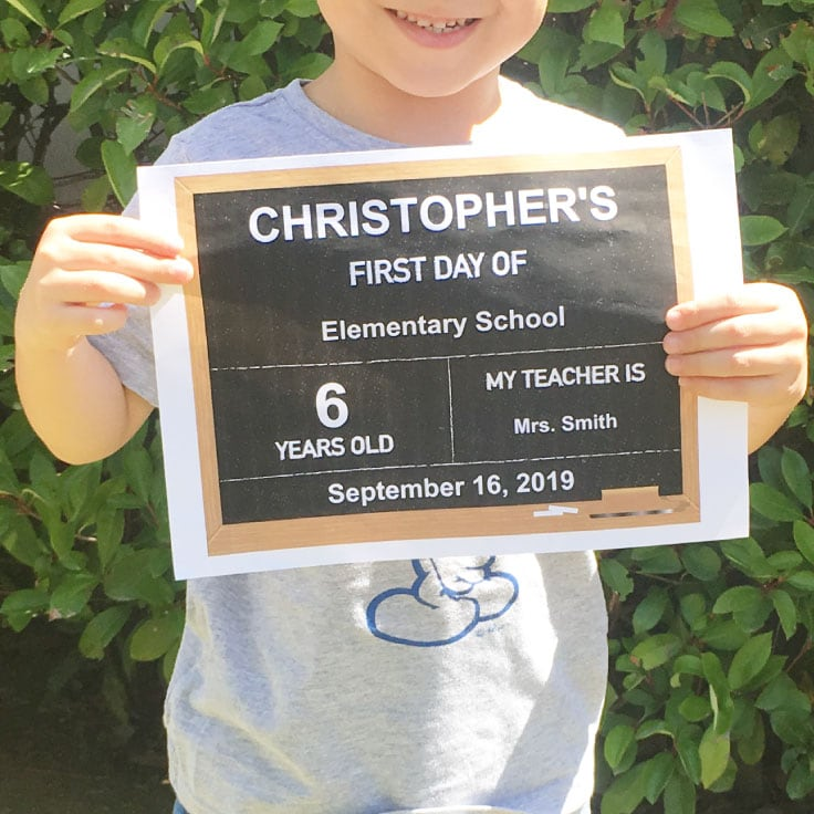 Kid holding first day of school chalkboard designed printable for a photo.