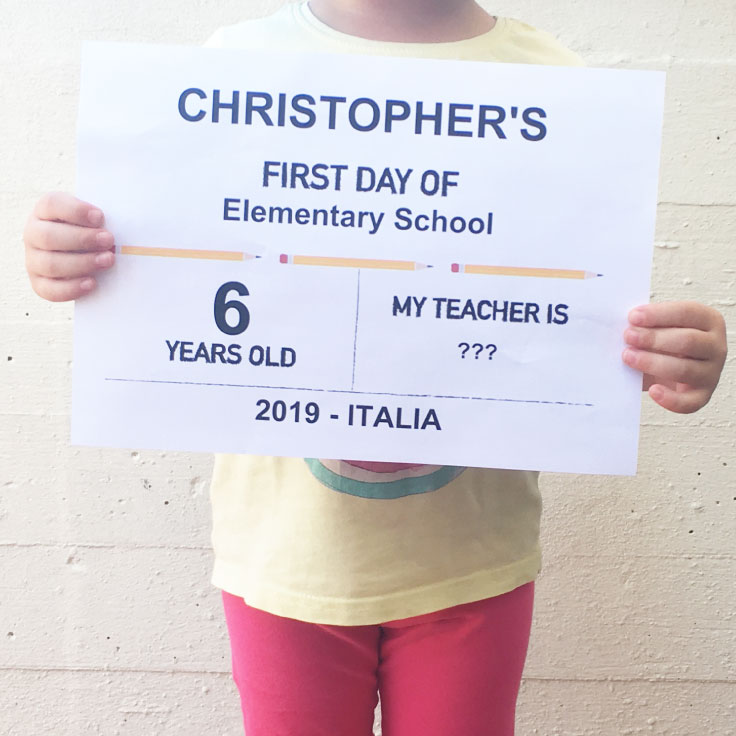 Child holding first day of school printable sign - pencils design.