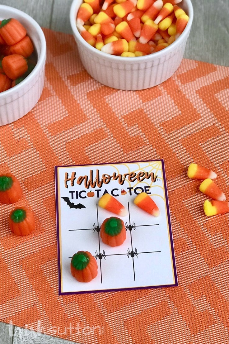 Candy pumpkins & candy corn and tic tac toe printable on an orange background.