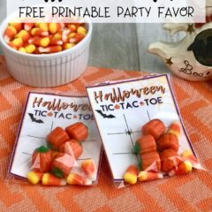 Assembled tic tac toe party favors with Halloween candy & game cards on an orange background.