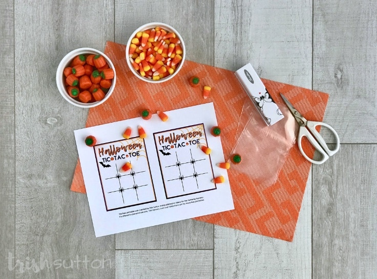 Halloween candy, tic tac toe printable, scissors and stapler on an orange background.