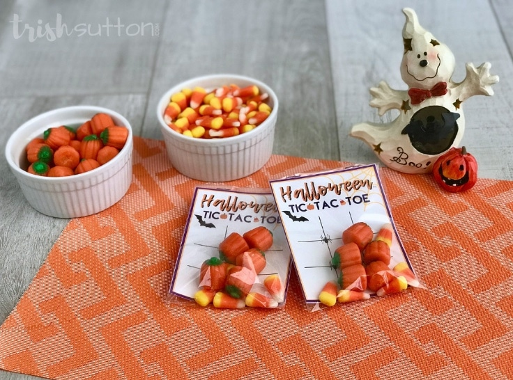 Tic Tac Toe party favors assembled in bags with candy and free printable on an orange background.