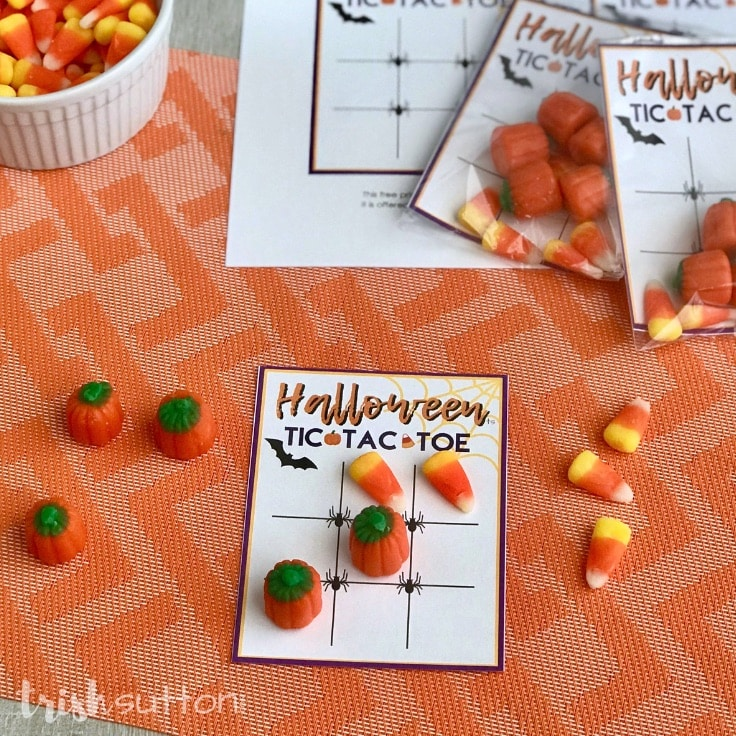 Halloween candy, tic tac toe printable and stapler on an orange background.