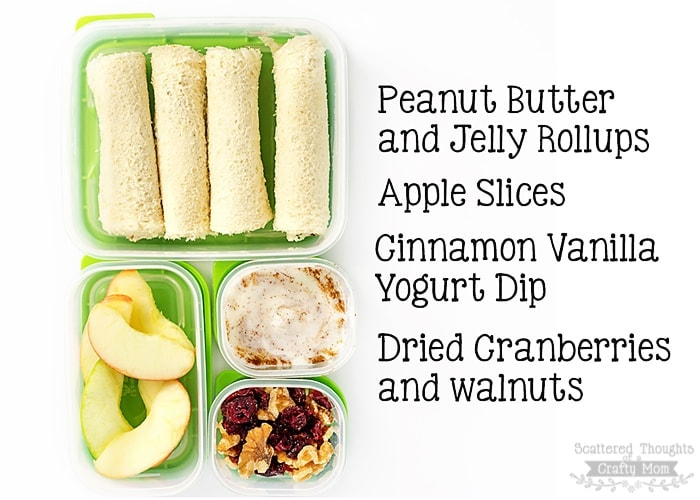School lunch idea of peanut butter jelly rollups, apple slices, yogurt dip, and a trail mix.