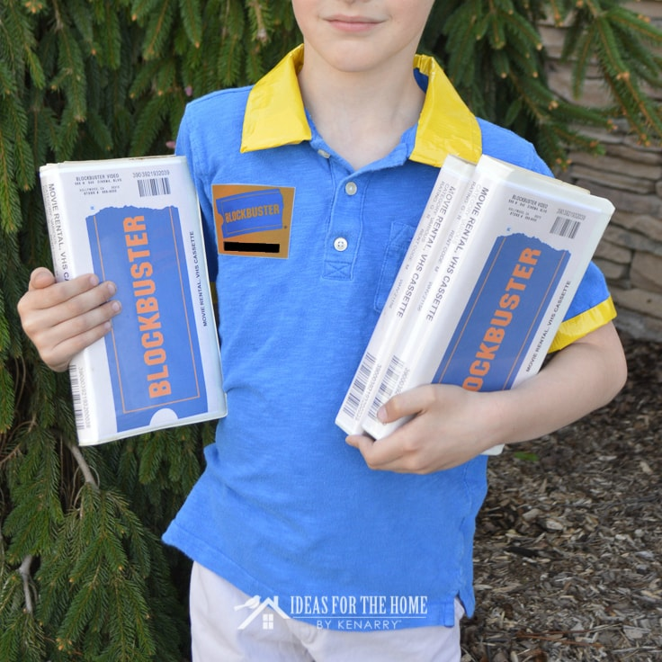 Boy wearing a Blockbuster video costume and holding VHS tapes