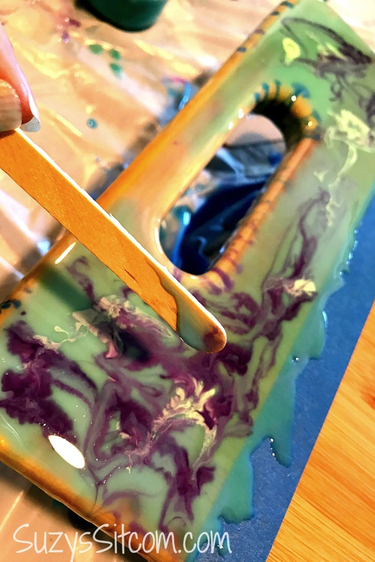 Using a craft stick to create a marbled effect with resin on a cutting board.