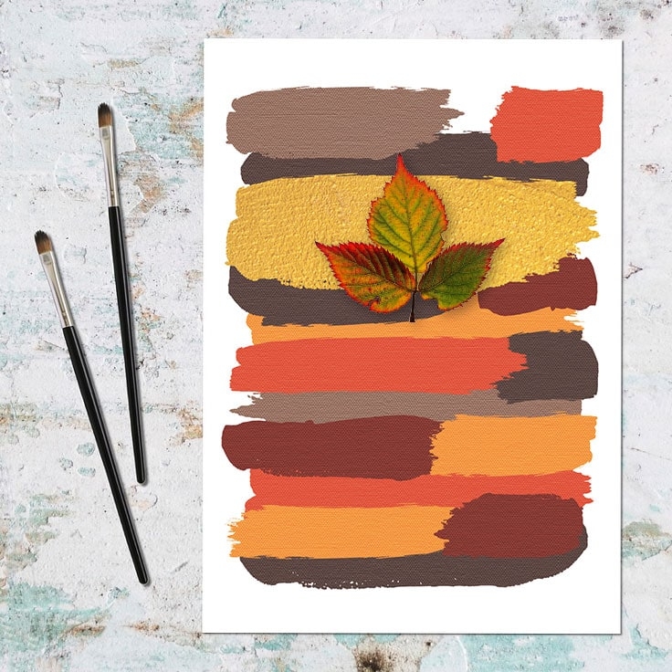 Abstract art print of earthy colored brushstrokes with 3 leafed twig on top and paintbrushes.