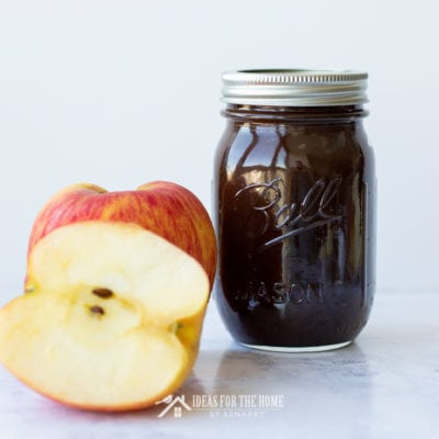 a partially cut apple picked from the orchard next to a full jar of apple butter